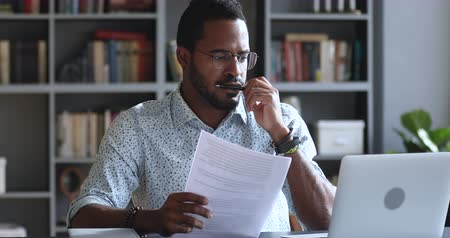 guy home : Serious focused african mixed race businessman student professional using laptop holding papers working sit at home office desk studying online doing research project preparing course work assignment