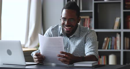 news letter : Happy amazed young african male student professional feel excited overjoyed read documents good news got new job receive salary rise payment taxes refund loan approval message sit at home office desk