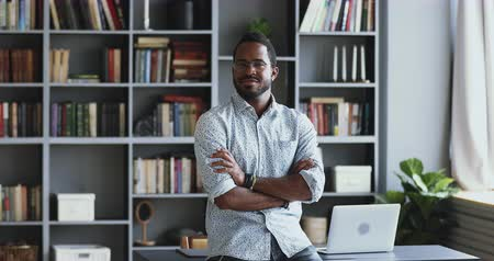 bibliotecario : Confident african businessman entrepreneur teacher stand in modern office with bookshelves look at camera, smiling young mixed race professional posing in work space arms crossed, business portrait