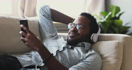 livros : Smiling young adult mixed race african man wear wireless headphones relax on sofa listening mobile music or learning foreign language audio course in smart phone app lying resting on couch at home