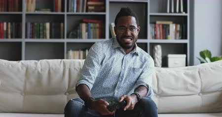 playstation : Funny excited young adult african mixed race man gamer winner holding joystick controller playing videogame sitting on sofa feeling overjoyed celebrating victory winning in video game alone at home Stock Footage