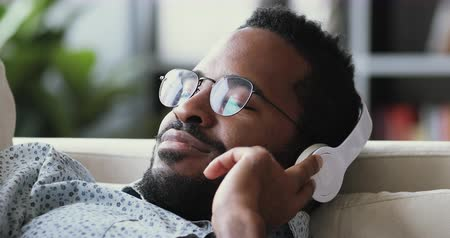 deep learning : Serene calm young african man wear wireless headphone relax with eyes closed meditate lying on sofa listen lounge music audio book course feel peace of mind no stress on couch at home, close up view