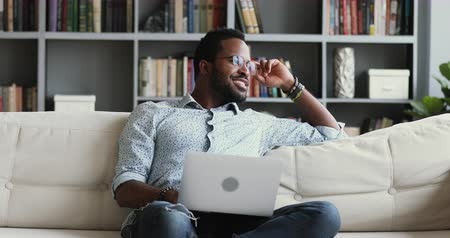 yazar : Happy dreamy successful young african american mixed race hipster man student freelancer look away at camera dreaming about good future opportunities thinking of inspiration sit on sofa using laptop