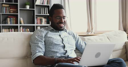 surfing the net : Happy young african male student using laptop notebook surfing social media relaxing at home, smiling mixed race man enjoying easy e learning browsing internet on modern technology device sit on sofa