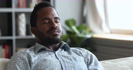 sentir : Calm relaxed young african american man meditate sit on sofa at home, serene tranquil mixed race guy doing breathing exercise take deep breath of fresh air rest with eyes closed on couch, close up Vídeos
