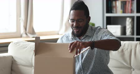 post room : Happy african man customer open cardboard box receive gift online purchase in postal parcel shipping delivery service concept, satisfied mixed race male consumer unpacking package sit on sofa at home Stock Footage