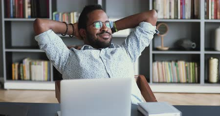 pauza : Relaxed young african businessman meditate sit at work desk with laptop hands behind head, satisfied mixed race office worker take break rest breath fresh air feel stress relief peace of mind concept