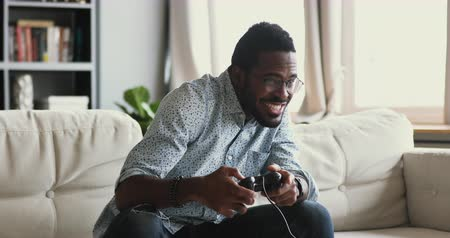 playstation : Happy emotional young adult african american guy gamer player holding joystick gamepad controller playing feel excited winning video game sit alone on couch at home, console videogames hobby concept Stock Footage