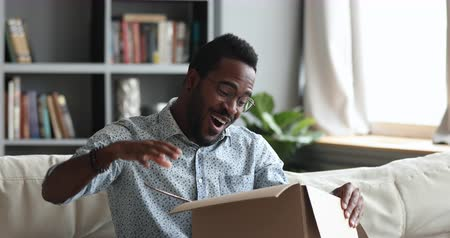 smíšené rasy osoba : Excited african male customer receive carton box with gift open post parcel sit on sofa at home, happy mixed race man consumer celebrate great retail online purchase fast shipment delivery concept