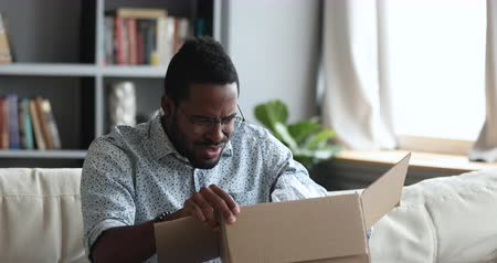 ошибки : Frustrated dissatisfied african man customer open cardboard box receive damaged wrong parcel, disappointed male consumer having problem with bad fake online shop post shipping delivery order concept Стоковые видеозаписи