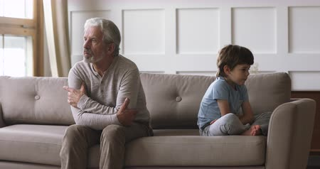 manipulacja : Upset old senior grandpa and offended small kid grandson sit on sofa not talking having two generation gap family conflict concept, elderly grandparent and little grandchild quarrel misunderstandings Wideo