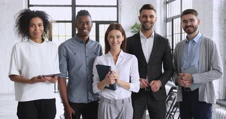 leden : Happy multiracial business team professional people colleagues stand together look at camera in modern office, smiling confident international diverse employees company staff group corporate portrait