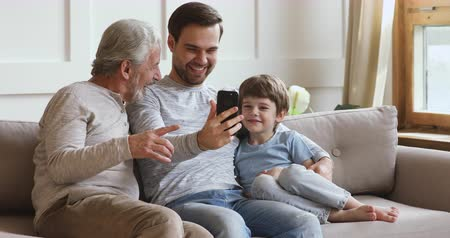три человека : Happy multi 3 age generation men family laughing using smart phone app sit on sofa, cute small child grandson, young adult dad and old senior grandpa having fun with modern mobile device tech at home Стоковые видеозаписи