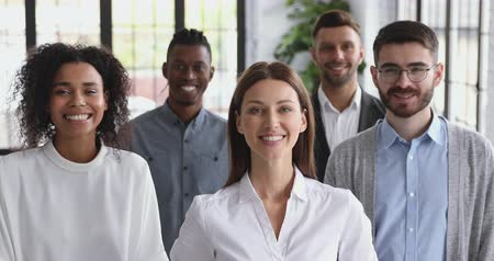 stage : Confident happy diverse business people posing together in office, smiling multiracial professional team colleagues and female leader stand together look at camera, staff group corporate portrait