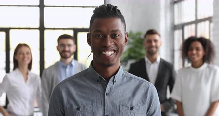 internar : Confident smiling millennial african american businessman looking at camera posing with team in modern office, happy ethnic young male professional leader coach trainer closeup business portrait