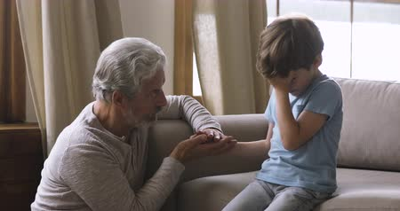 представитель старшего поколения : Loving worried old grandpa holding hand comforting sad crying little grandson talking to upset grandchild help console apologize say sorry, grandparent and grandchild support reconciliation concept