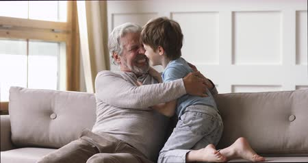 unokája : Cheerful old senior grandpa and cute little boy grandson laughing playing at home, two generations family elder grandfather having fun with grandchild tickling sit on sofa enjoying leisure lifestyle Stock mozgókép