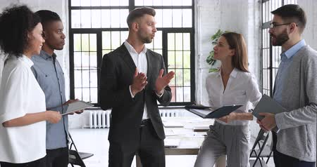 supervisora : Confident businessman leader coach mentor boss wear suit giving instructions talking to happy diverse sales team business people in office explaining project plan at corporate group stand up meeting