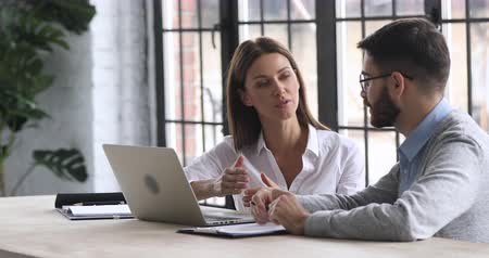 продавщица : Confident businesswoman professional sales manager talking to male client customer consulting businessman helping colleague offering insurance loan services sit at desk office meeting with laptop
