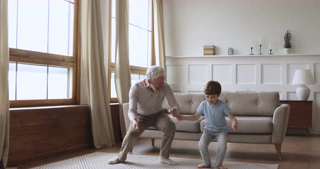 friendship dance : Happy two age generations active family dancing in living room, carefree old senior adult grandfather and cute preschool grandson having fun listening music jumping enjoying time together at home