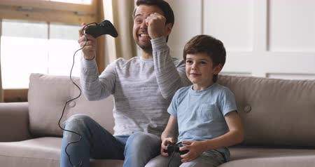 playstation : Overjoyed young adult dad and cute child son gamers winners playing winning video game, excited father having fun with kid boy give high five holding joysticks celebrating videogame victory at home