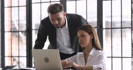 collaborating : Male boss mentor helping female employee with online assignment teach intern in office, businessman executive supervisor helping businesswoman coworker with laptop at workplace check work progress