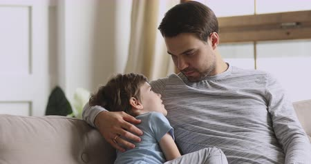 compreensão : Caring happy young adult dad embracing small preschool child son having trust conversation cuddling sit on sofa, loving father enjoy talking with little kid boy enjoy honest communication concept