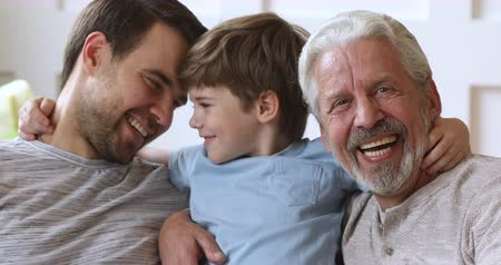 home grown : Cheerful intergenerational 3 three generation men family closeup portrait, happy little boy son grandson cute face embrace young father and old grandpa look at camera laugh hug bond together at home Stock Footage