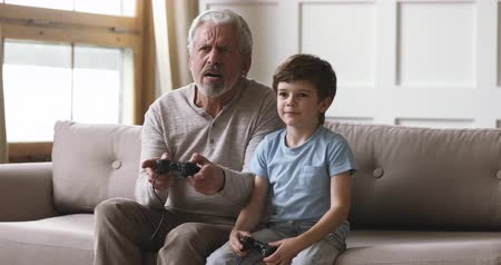 playstation : Emotional happy old senior grandpa and cute little kid grandson gamers team hold joysticks controllers play video game sit on sofa, two age generations family having fun enjoy videogame at home