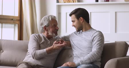 compreensão : Friendly honest old father and young son talking on sofa, happy two generations male family having trust conversation chatting relaxing on couch in living room enjoy understanding and support concept Stock Footage