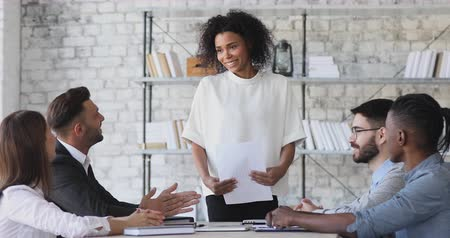 ovation : Happy pleased female african american boss get team applause after financial report presentation at group meeting, multiethnic employees team clapping hands thanking mentor at conference room table