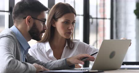 stage : Male professional mentor helping female client teach intern training new worker consult customer explain online business services computer corporate software look at laptop screen at office meeting