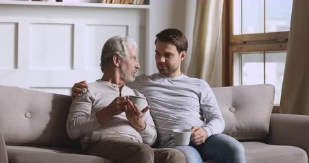 honesto : Serious happy two generation men family hold drinks having trust honest conversation chatting sit on sofa at home, senior old parent father talking to young adult grown son share news relax on couch