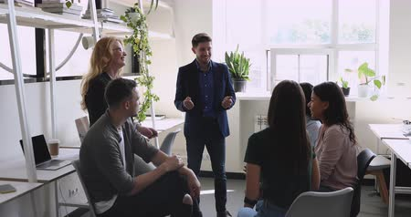 поощрение : Confident male leader company executive speaking to diverse friendly team people gather in office motivating happy multiethnic work group explaining new corporate plan training employees at meeting Стоковые видеозаписи