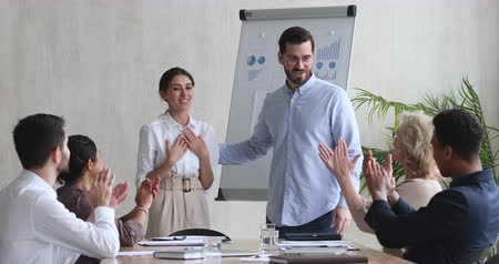 juntar : Proud grateful young female worker get promotion evaluation applause handshake executive boss at team office meeting, satisfied male ceo motivate praise happy best employee give feedback concept