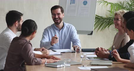 сотрудники : Happy male ceo boss manager telling funny joke having fun talking with multiethnic employees during group briefing, cheerful friendly diverse business team people laughing sitting at meeting table