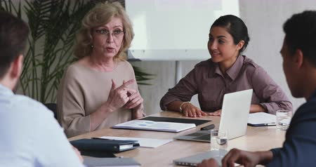 starszy pan : Skilled professional old middle aged female mentor executive teaching employees group explain company strategy training staff team, mature businesswoman conduct corporate workshop sit at office table Wideo