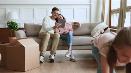 uitpakken : Happy little children daughters playing with cardboard boxes while young parents sit on sofa using tablet on moving day in new home apartment living room, family relocation and removals concept