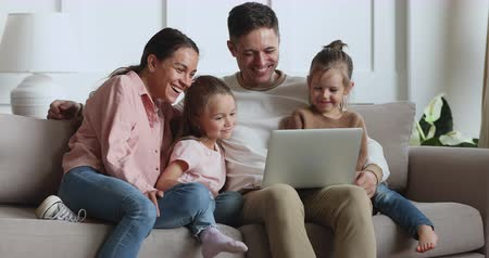 ailelerin : Happy cheerful family young adult parents couple and cute little children daughters laughing using laptop looking at computer watching funny movie online bonding relaxing on sofa at home together Stok Video