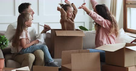 uitpakken : Cute small kid daughter jumping out of cardboard box on moving day playing with adult parents and child sister having fun enjoying family renters relocating in new home unpacking on couch together
