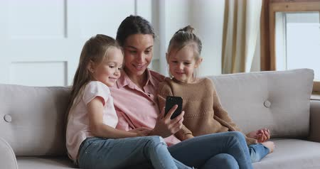 bloggers : Happy young mum using social media app on smartphone recording video blog having fun with two cute small children daughters embracing bonding together looking at mobile phone relaxing on sofa at home