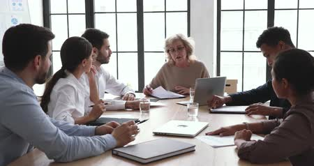 placa : Serious mature senior company ceo talk at diverse group board meeting explain professional management strategy contract benefits to clients corporate plan financial report at conference office table