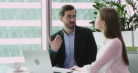 internat : Businessman wearing suit mentor manager teacher talking to young businesswoman training teaching intern student consult customer helping coworker having business conversation at workplace with laptop
