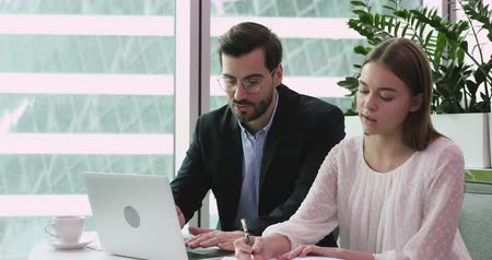 stage : Male mentor coach manager teaching female intern helping coworker giving instructions advice pointing at laptop learning new corporate software make notes sit at office workplace, internship concept