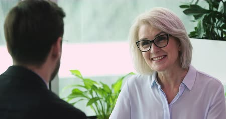 dojem : Smiling friendly older businesswoman hr employer having business conversation with businessman job applicant client or partner discussing qualifications make good first impression at business meeting