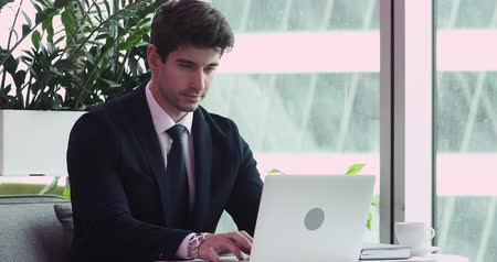 banqueiro : Successful young handsome businessman wear suit working online on laptop computer sit at office desk, focused stylish male executive typing on notebook using business technology at modern workplace