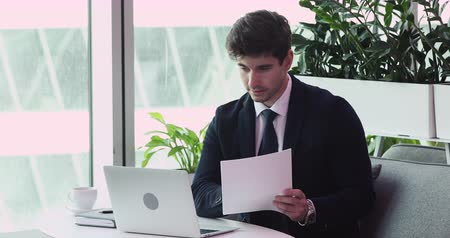 factuur : Serious young businessman lawyer wear suit holding reading document checking legal paper report sitting at office desk, focused company ceo doing paperwork working on computer in modern office