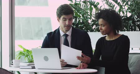 persuasion : Male caucasian lawyer salesman banker or employer wear suit consulting female african customer offering employment job contract lease loan agreement sell insurance bank services at business meeting Stock Footage