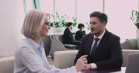 persuasion : Businessman employer hr listen old middle aged businesswoman job candidate speak during job interview, mature female financial advisor give professional advice consult client at business meeting