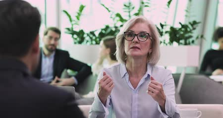 persuasion : Confident mature senior businesswoman lawyer consulting client about contract, serious middle aged hr manager mentor explaining deal benefits interview applicant teaching employee at business meeting